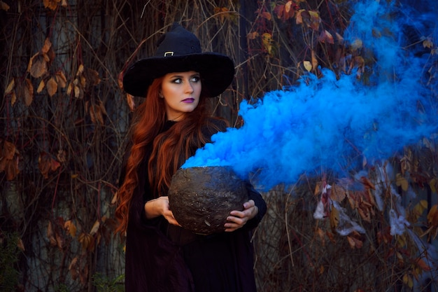 A girl in a black witch costume and a pointed hat with a pot of blue smoke on halloween in autumn park