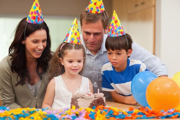 女の子は彼女の誕生日のケーキにキャンドルを吹き飛ばした