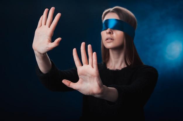 Девушка с завязанными глазами, с голубой лентой, ищет что-то своими руками, играет, развлечение, загадка
