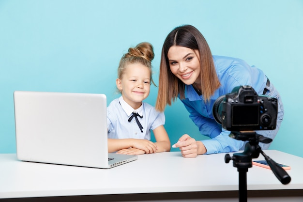 Girl blogger recording vlog on the camera sitting with laptop and mother helping her to look good.