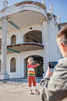 Girl blogger records film and makes selfie over abandoned building for her channel local tourism