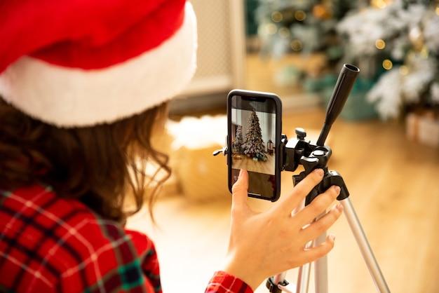 女の子のブロガーは、クリスマスツリーの背景に彼女の携帯電話でビデオや写真を撮影します。彼女はサンタクロースの帽子をかぶった。