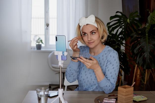 女の子のブロガーが購読者にスキンケアとメイクアップについて語るブログ、放送、化粧品のコンセプト