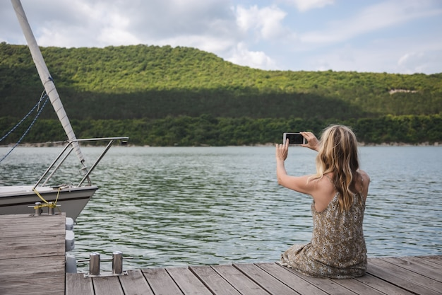 Girl blogger traveler sits on a pier and takes pictures on a smartphone