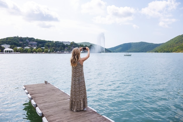 Girl blogger traveler stands on the pier and takes pictures on a smartphone