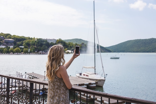 Girl blogger traveler takes pictures on smartphone