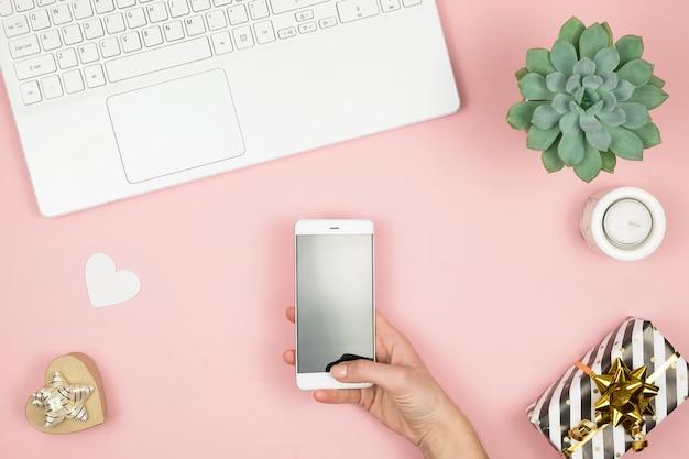 レディースホームワークスペース。 girl bloggerは、電話とラップトップで動作します。フリーランスのコンセプト。オンラインで作業するラップトップとインターネットを使用したテレワーカーテキストメッセージ。