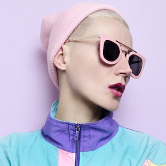 Girl blonde in fashionable hat beanie and pink glasses vanilla vibration