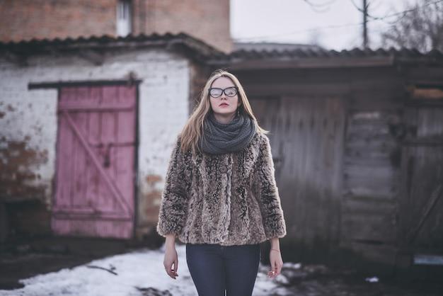 Девушка блондинка в очках кошачьих глаз в искусственной шубе позирует