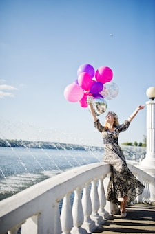 Girl blonde with balloons at hen party against lake.