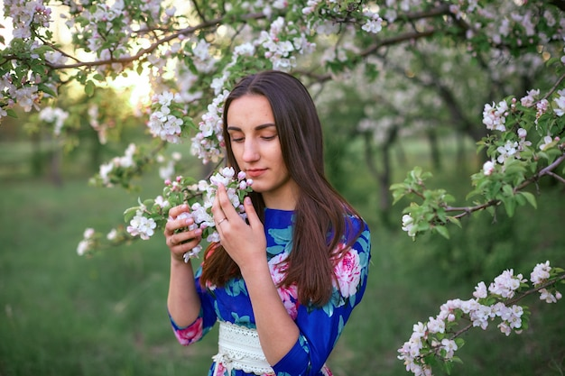 Girl in a blooming apple orchard at sunset