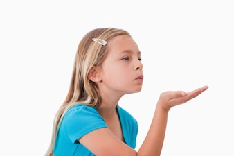 Girl blowing a kiss against a white background