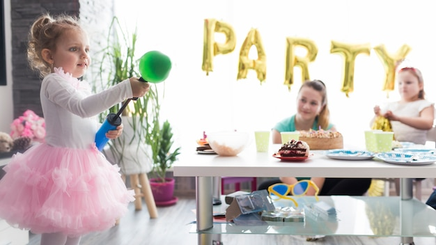 Girl blowing balloons on birthday party