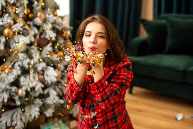 紙吹雪を吹く少女。彼女は居間で新年とクリスマスを祝っています。背景のクリスマスツリー