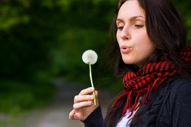 Girl blowing on  dandelion. lifestyle concept
