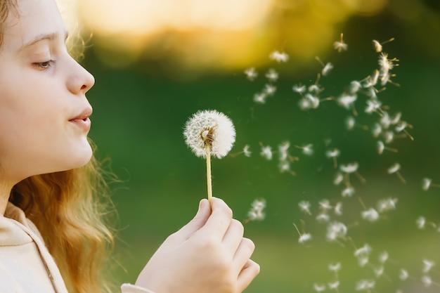 Girl blowing dandelion in spring park medical healthy concept