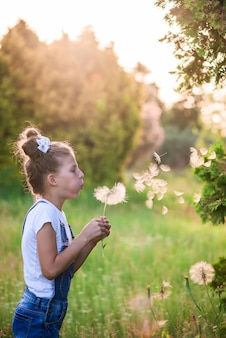 Girl blowing on a dandelion.