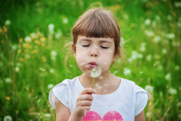 Girl blowing dandelions in the air. selective focus.