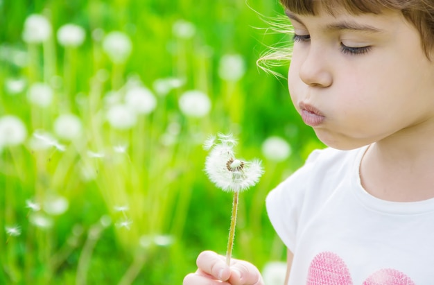 Girl blowing dandelions in the air