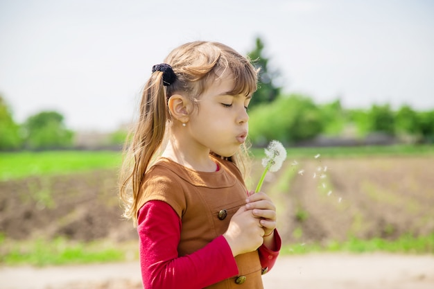 Girl blowing dandelions in the air.