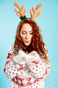 スタジオショットで偽の雪を吹く少女