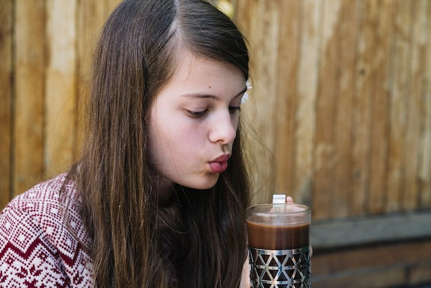 Girl blowing over the hot chocolate drink