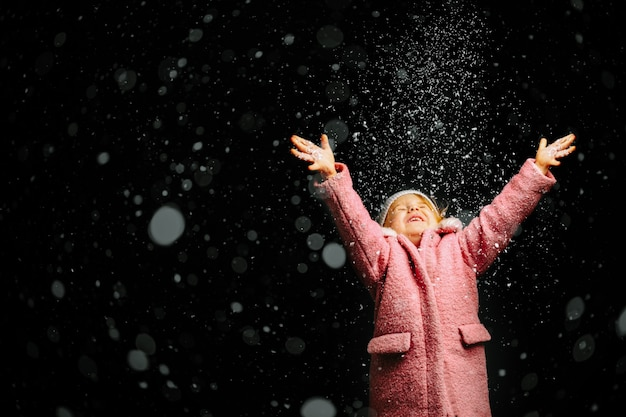 Girl blowing in the snow on a black background on christmas eve