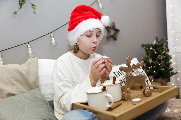 Девушка задувает свечу в шапке деда мороза