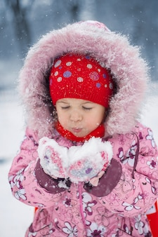 The girl blows on snow in hands