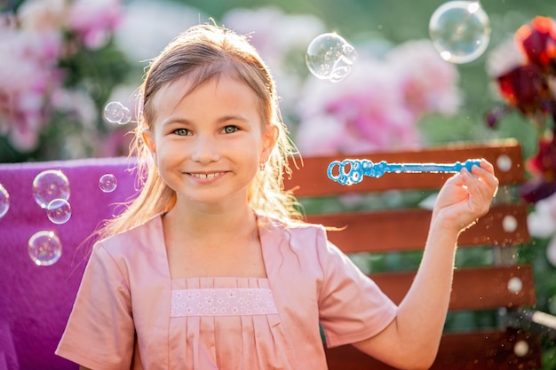 Girl blows soap bubbles against flowers in the garden. on the face of emotions of surprise and admiration.