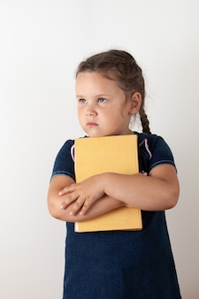 A girl in a blue denim dress holds an orange book in her hands and holds it to her chest, looking up. sad child, isolated