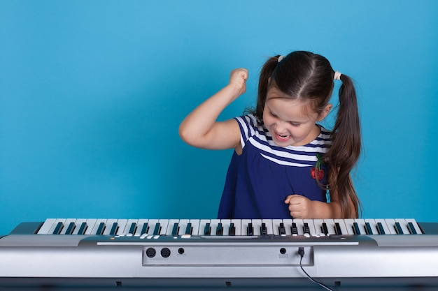 Girl in a blue dress beats her fists on the synthesizer keys with anger