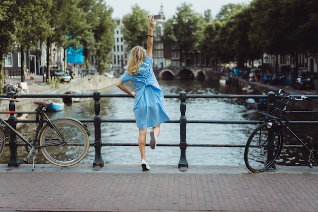 Girl in a blue dress on the bridge in amsterdam