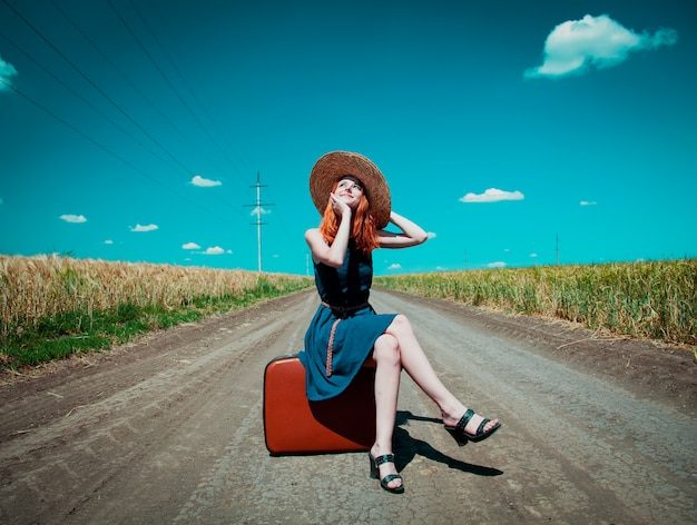 Girl in a blue dress and a hat with a suitcase on the rural road