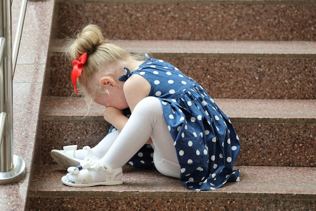 Girl in a blue dress sits on the steps and cries