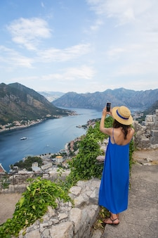 A girl in a blue dress and a straw hat stands against the backdrop of the very beautiful bay of kotor in montenegro and takes pictures with her phone.