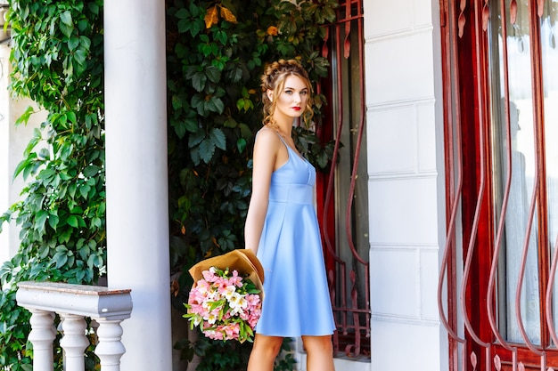 Girl in blue dress with bouquet of flowers on the street