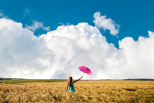 Girl in blue dress with red umbrella on the wheat field in sunlight.