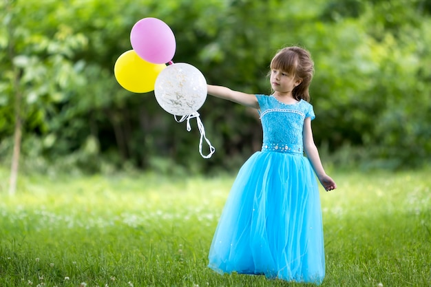 Girl in blue evening dress holding colorful balloons