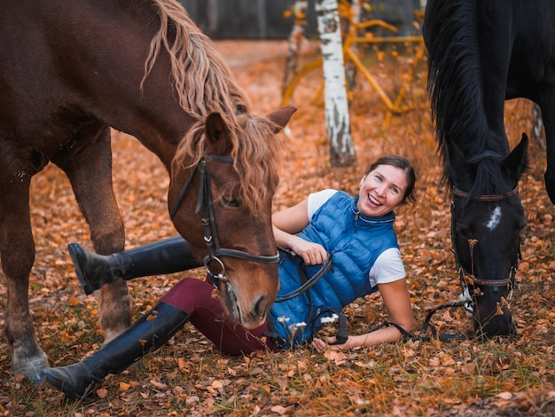 A girl in a blue jacket lies next to the horse and laughs.