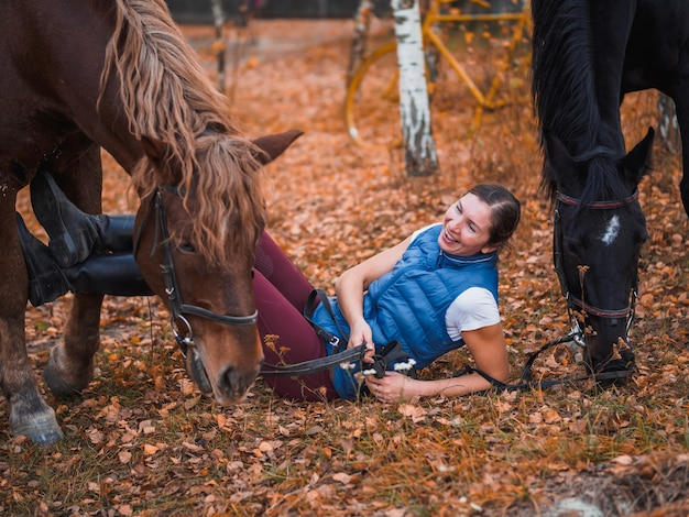 A girl in a blue jacket lies next to the horse and laughs. Premium Photo