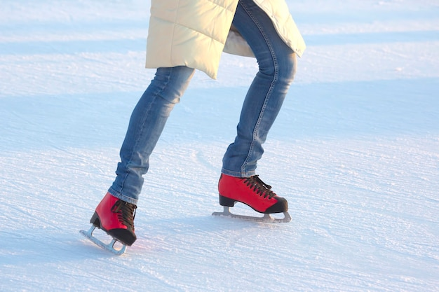 Girl in blue jeans actively skates on red ice skates on an ice rink. sport and hobbies. holidays and winter fun
