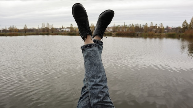 A girl in blue jeans sits by the lake. a young woman is resting by the river, sitting on the edge of a wooden bridge. pair of legs relaxing by a lake on a wooden dock. people are resting.