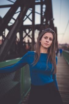 Girl in a blue long sleeve shirt on a street. urban sunset portrait.