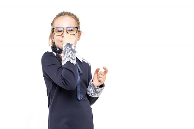 Girl in a blue school uniform emotionally posing on a white background