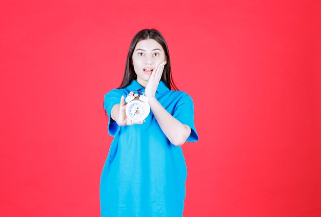Girl in blue shirt holding an alarm clock and realizing she is late