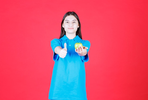 Girl in blue shirt holding a green apple and showing positive hand sign