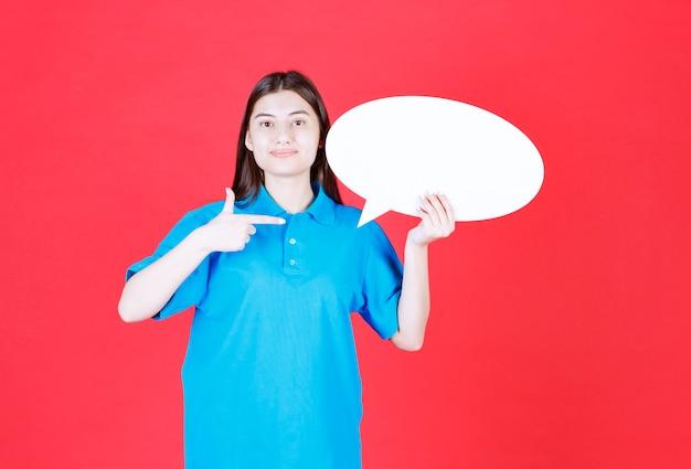 Ragazza in camicia blu con in mano un pannello informativo ovale