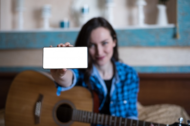 Girl in blue shirt and jeans with acoustic guitar shows hand with smartphone.