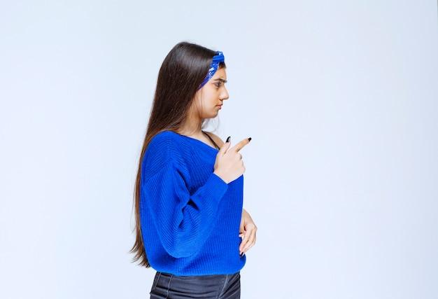 Ragazza con la camicia blu che indica qualcosa sulla destra.